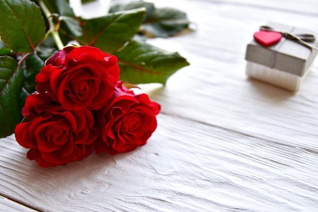 赤い木のバラと白い木製のギフトボックス。バレンタインデーのコンセプト Premium写真