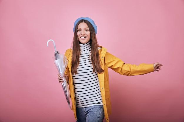 閉じた傘と黄色のレインジャケットで陽気なかわいい女の子が実行されています。 Premium写真
