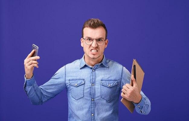 Раненый парень держит серый сотовый телефон и коричневую тетрадь Premium Фотографии