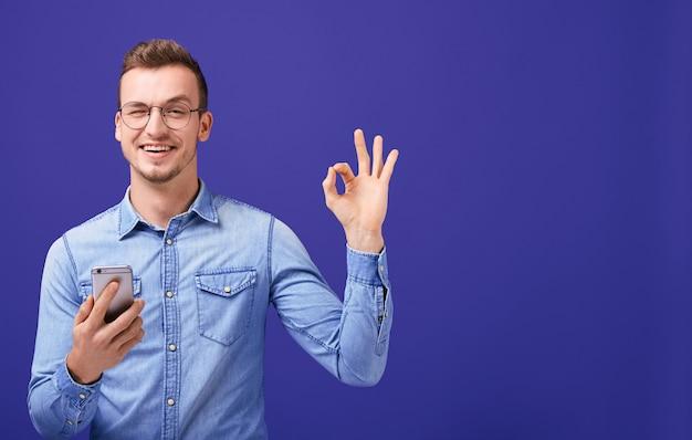 Молодой человек в джинсовой рубашке держит мобильный телефон в руке и показывает нормально Premium Фотографии