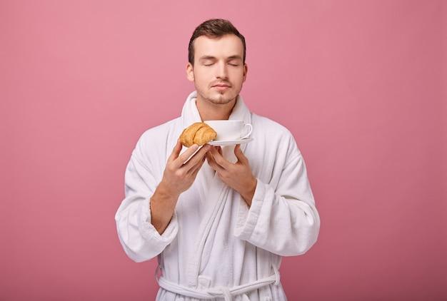 Крутой парень в белом с ароматным круассаном в одной руке и белой чашкой и блюдцем во второй Premium Фотографии
