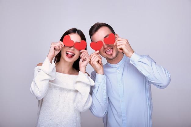 Безумно потрясающая пара влюбленных, держащая в руках возле глаз красные картонные сердечки, праздник святого валентина. Premium Фотографии