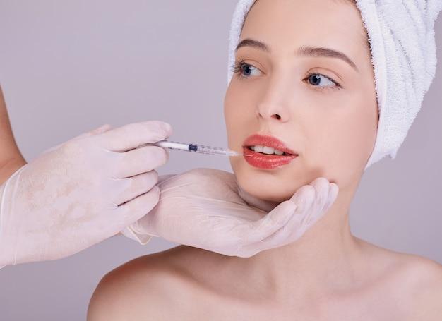 美容師の医師が若い女性の唇に注射をします。 Premium写真