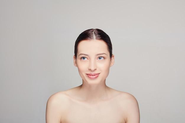 自然化粧品で美しい女性。清潔で新鮮な肌、暗い耳、青い目を持つ女性。 Premium写真