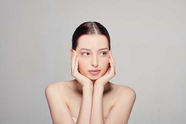 両手で彼女の顔に触れる青い目の新鮮なきれいな肌と美しい若い女性。 Premium写真