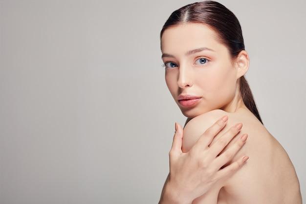 青い目と完全な唇を持つ若い美しい女性は、彼の肩に手を握っています。 Premium写真