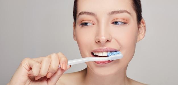 彼女の手に歯ブラシを持つ女性はほぼ白い歯と彼女の口 Premium写真