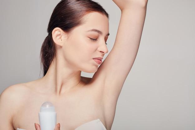 彼女の手で消臭剤とグレーでポーズきれいな新鮮な肌と茶色の髪を持つ女性 Premium写真
