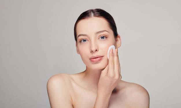彼女の右手に綿のパッドを持つクローズアップ若い美しい優しい穏やかな女性に青い目でまっすぐに見える、 Premium写真