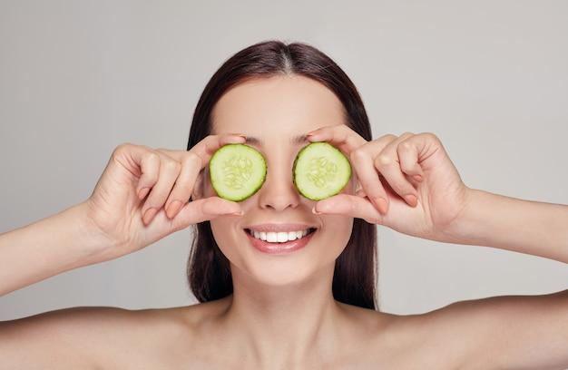 唇と遊び心のある気分で黒髪の魅力的な女性。女性はキュウリのスライスから眼鏡を作り、白い歯で笑顔を作りました。若返り、スパ、化粧品。コピースペース Premium写真