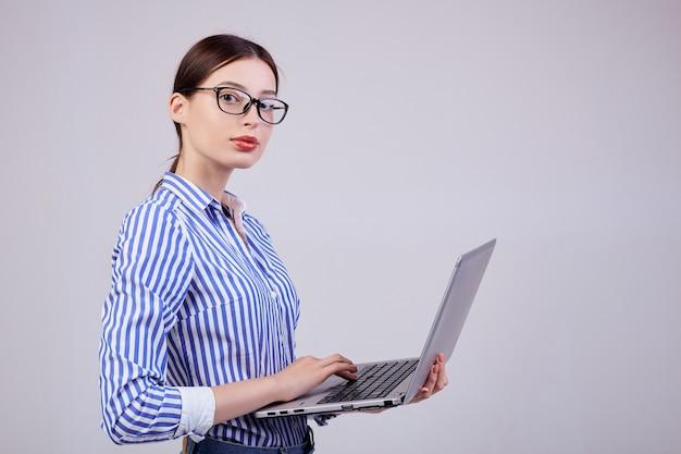 メガネとグレーのラップトップとストライプホワイトブルーシャツの女性管理者の肖像画。今年の従業員、ビジネスの女性。 Premium写真