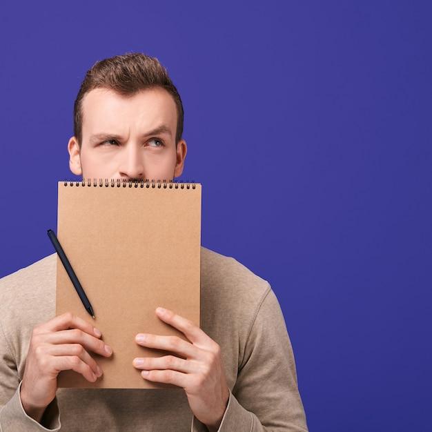 ハンサムな男は茶色のノートを保持しています。 Premium写真