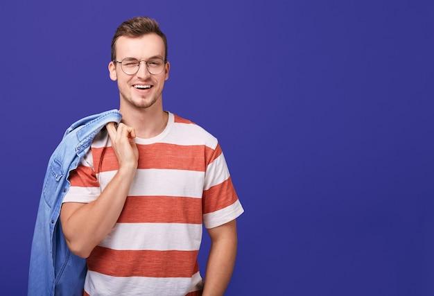Красивый мужчина в полосатой футболке и очках подмигивает и улыбается. Premium Фотографии