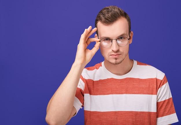Человек смотрит на камеру, держась за очки. Premium Фотографии