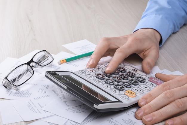 Непознаваемый бизнесмен используя калькулятор на офисе стола и писать делает примечание с высчитывает о стоимости дома офисе. Premium Фотографии