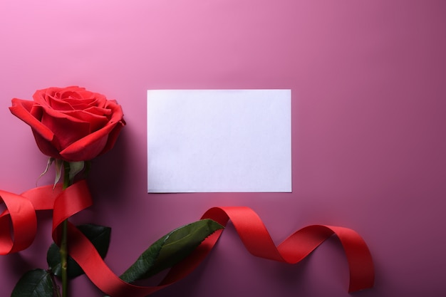 Символы влюбленности поздравительной открытки предпосылки дня валентинки, красное украшение с розами на розовой предпосылке. вид сверху с копией пространства и текста. плоская планировка Premium Фотографии