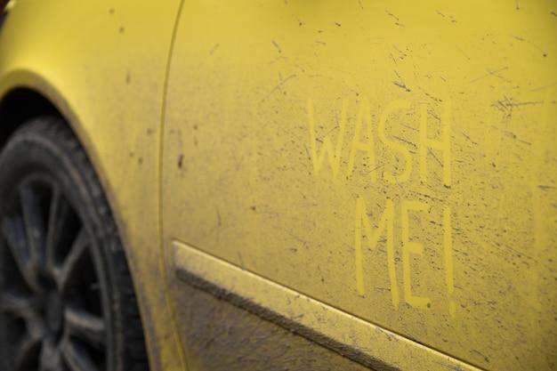 車の非常に汚れた表面に碑文のテキスト「ウォッシュミー」を書きます。コンセプトカーウォッシュ。 Premium写真