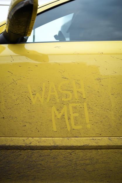 Напишите слова с надписью «помой меня» на очень грязной поверхности автомобиля. концепт автомойки. Premium Фотографии