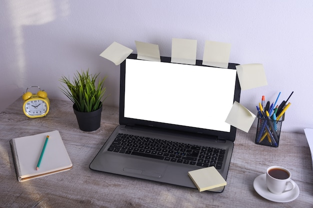Современный белый офисный стол макет таблицы, рабочее место с ноутбуком с белым экраном для вас текст или изображение, зеленая трава, чашка кофе и стопку бумаг на фоне белой скалы. Premium Фотографии