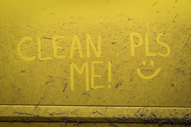Напишите слова с надписью «очистите меня» на очень грязной поверхности автомобиля. концепт автомойки. Premium Фотографии