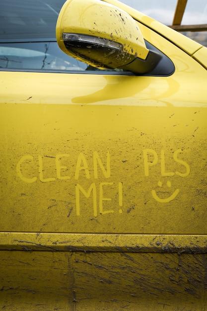 車の非常に汚れた表面に碑文のテキスト「私をきれいに」を書きます。コンセプトカーウォッシュ。 Premium写真