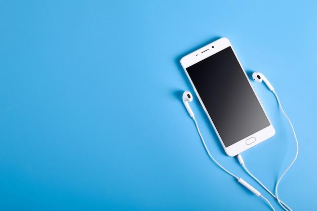 テキスト用の場所と明るい色の青色の背景にモバイルヘッドフォンと白い色の携帯電話。 Premium写真