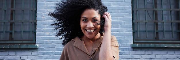 笑いと楽しんでアフロ髪の若い黒人女性 無料写真