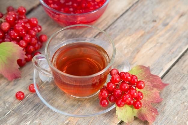 Чашка травяного красного чая и ягод калины с миской джема Premium Фотографии