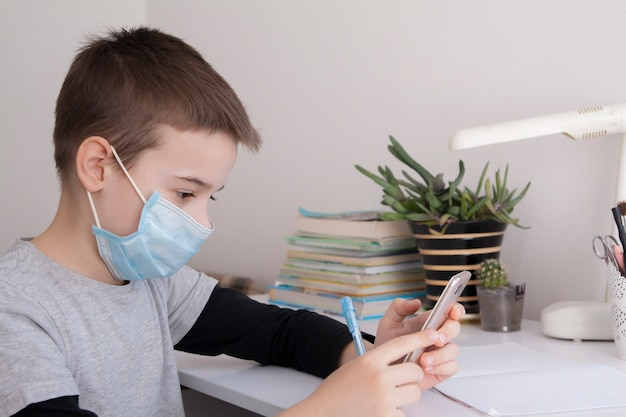 Мальчик дома обучение с смартфон в его руках и медицинская маска. концепция карантина коронавируса Premium Фотографии