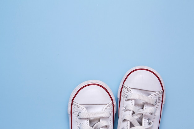 青色の背景に子供の靴の前。子供の靴、服、散歩についてのテキストのためのスペースをコピーします。 Premium写真