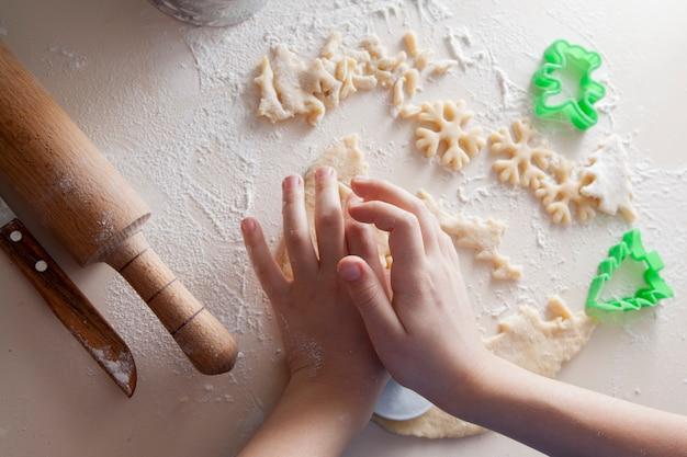 Ребенок режет печенье снежинками. рождественская выпечка Premium Фотографии