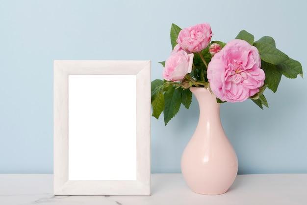 Фоторамка возле вазы с цветами на столе на синем фоне стены Premium Фотографии