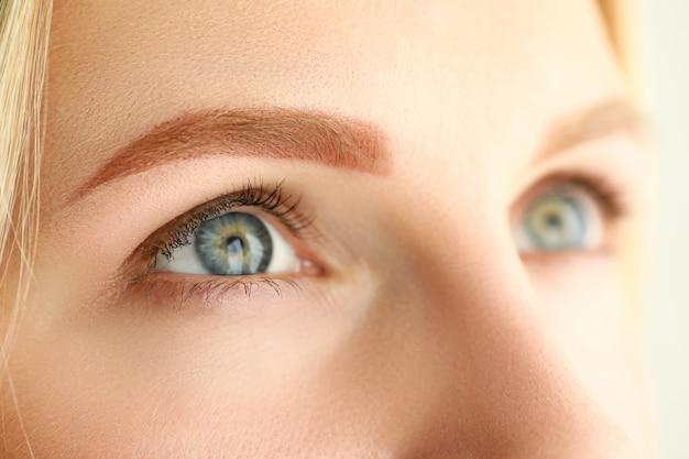 Конец-вверх молодой женщины при совершенная русая бровь смотря вверх. съемка макроса женщины после процедуры ухода за лицом красоты. косметология перманентного макияжа и концепция велнес Premium Фотографии