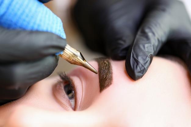 Косметологи руками делают перманентный макияж бровей Premium Фотографии