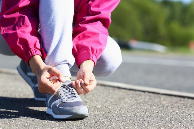 路上で靴ひもを結ぶ若い女性 Premium写真