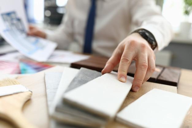 Мужская рука держит керамическую плитку крупным планом Premium Фотографии