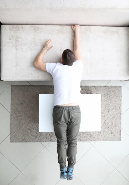 Мужчина лежит на диване и на столе Premium Фотографии