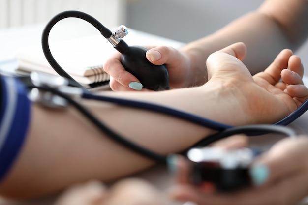 Медсестра измеряет давление больному человеку Premium Фотографии