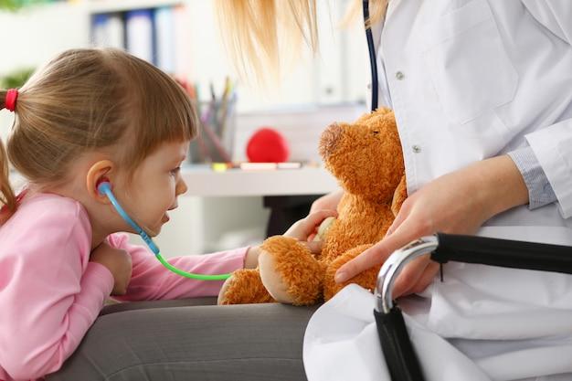 Женская рука стетоскопа владением маленькой девочки слушает Premium Фотографии