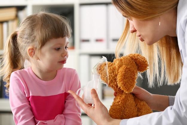 医師がおもちゃに吸入器を与える小さな患者と遊ぶ Premium写真