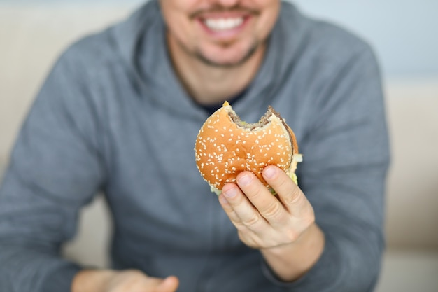 新鮮なハンバーガーを手に保持笑みを浮かべて男 Premium写真