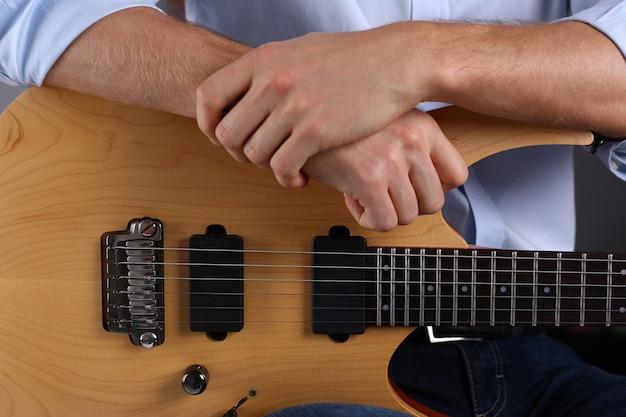 Мужские руки играют на электрогитаре классической формы Premium Фотографии