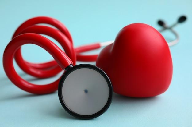 Красный стетоскоп с сердцем на синем современном фоне Premium Фотографии