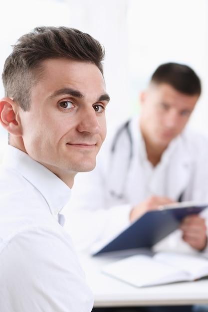 彼のオフィスで医者と満足のハンサムな笑みを浮かべて男性患者。高レベルおよび質の高い医療サービスのセラピストの相談の仕事とキャリアの物理的な健康的なライフスタイルのコンセプト Premium写真