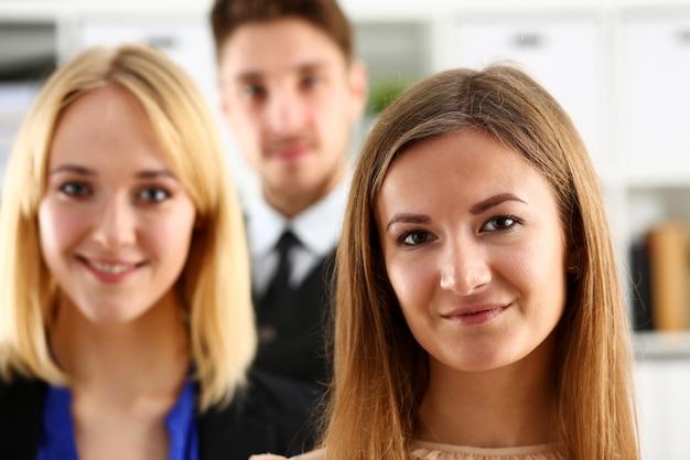 笑顔の人々のグループは、カメラで見ているオフィスに立つ Premium写真