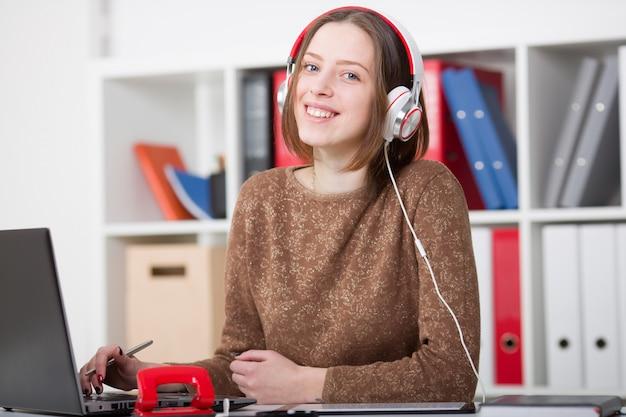 音楽を聴くと学習のヘッドフォンで美しい女子学生 Premium写真