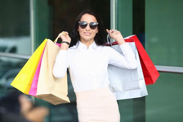 Портрет улыбается женщина, носить стильные очки и классические белые блузки. красивая модель, держа в руках красочные сумки после посещения магазинов. Premium Фотографии
