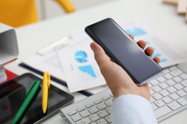 Бизнесмен держит новый смартфон в Premium Фотографии