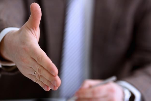 スーツとネクタイの男は、オフィスのクローズアップでこんにちはとして手を与えます。友人歓迎調停の積極的な紹介感謝ジェスチャーサミット参加承認動機男性アームストライクバーゲン Premium写真