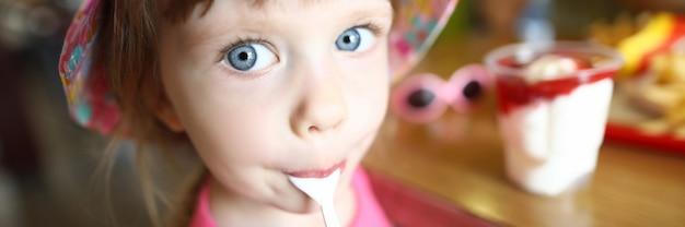 満足している小さな子供が氷でスプーンをなめる Premium写真